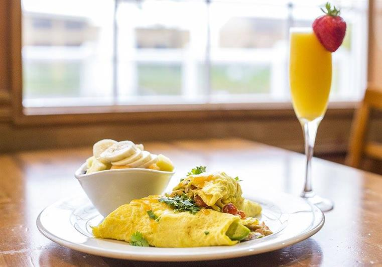 Omelette on a plate with a side of fresh fruit and a mimosa.