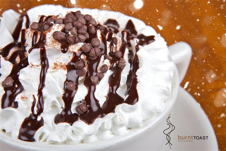 Mocha latte in a white cup topped with whipped cream, chocolate syrup and chocolate chips.