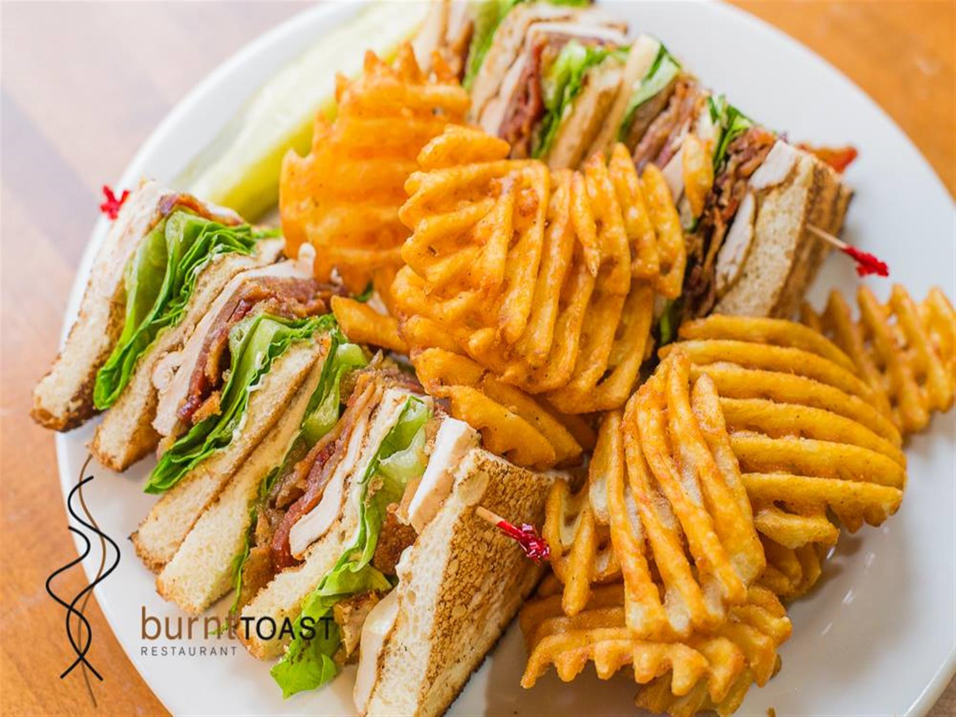 Turkey club sandwich with lettuce, bacon and mayo with waffle fries and a pickle spear