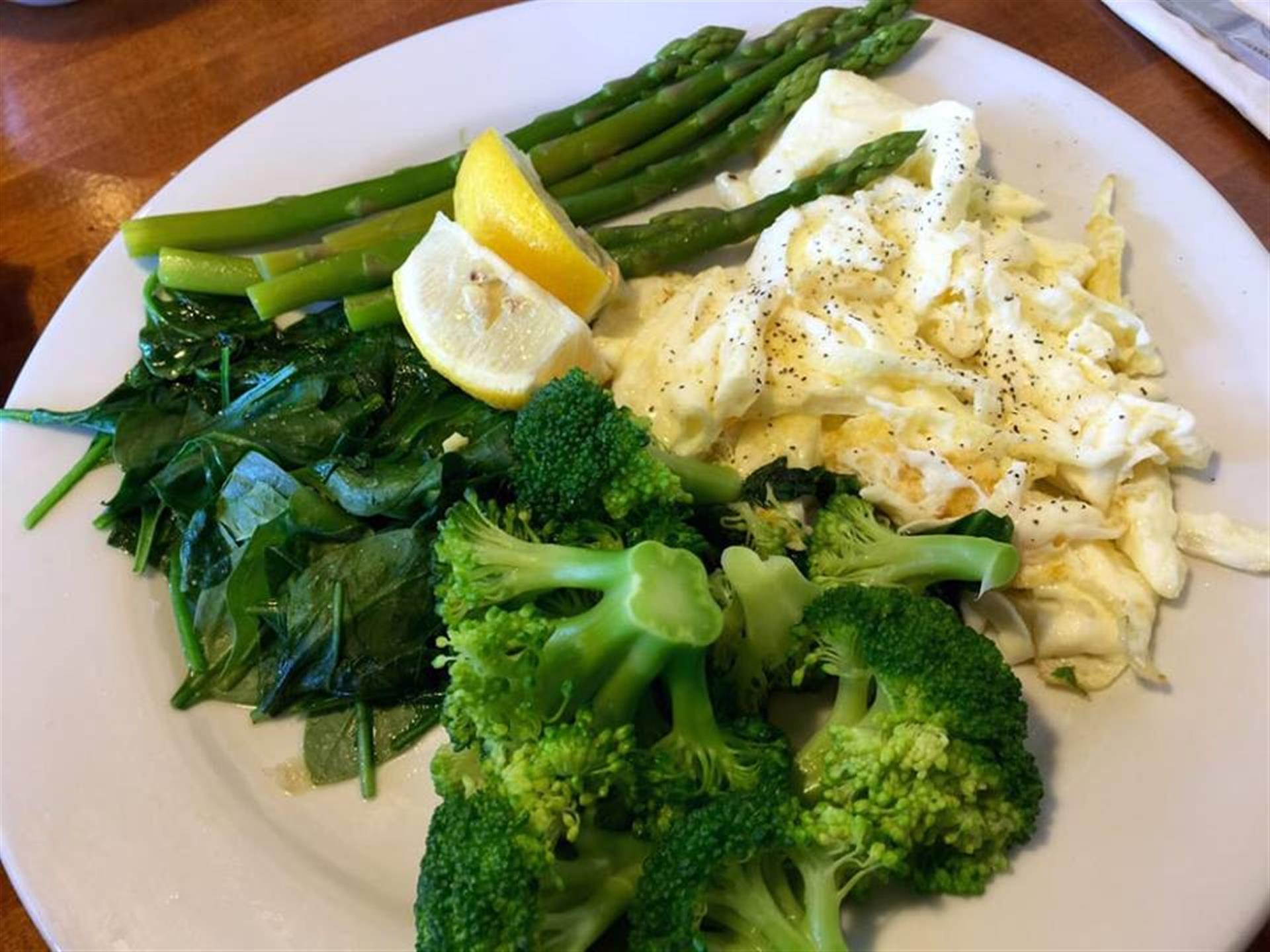 Scrambled egg whites with spinach, broccoli, lemon wedge and asparagus