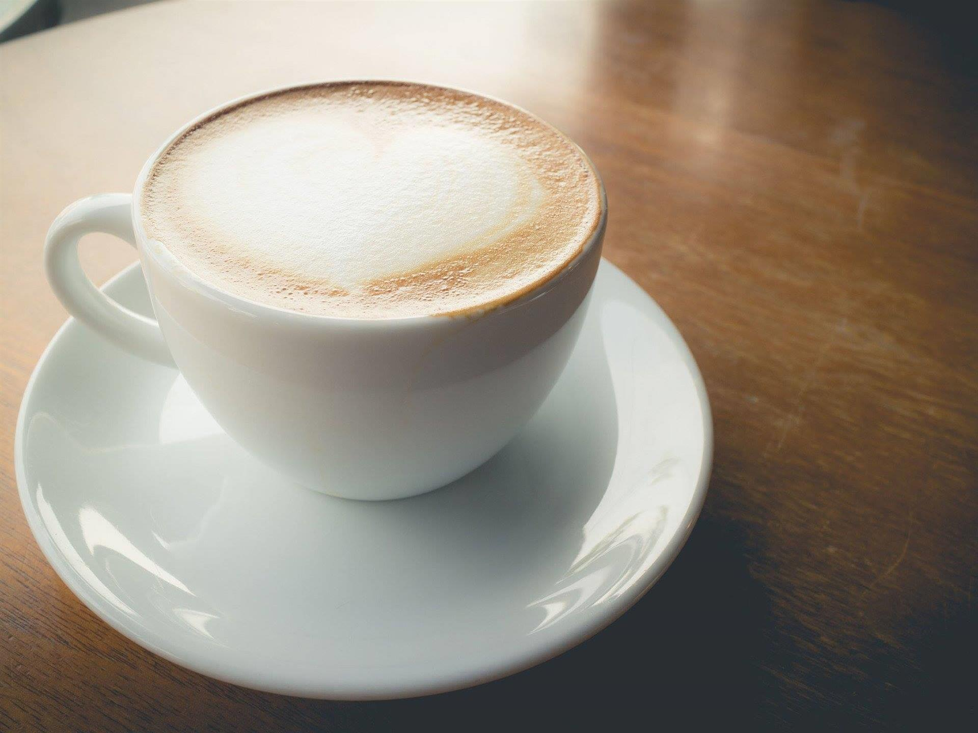Cafe latte in a coffee cup on a wooden table-top