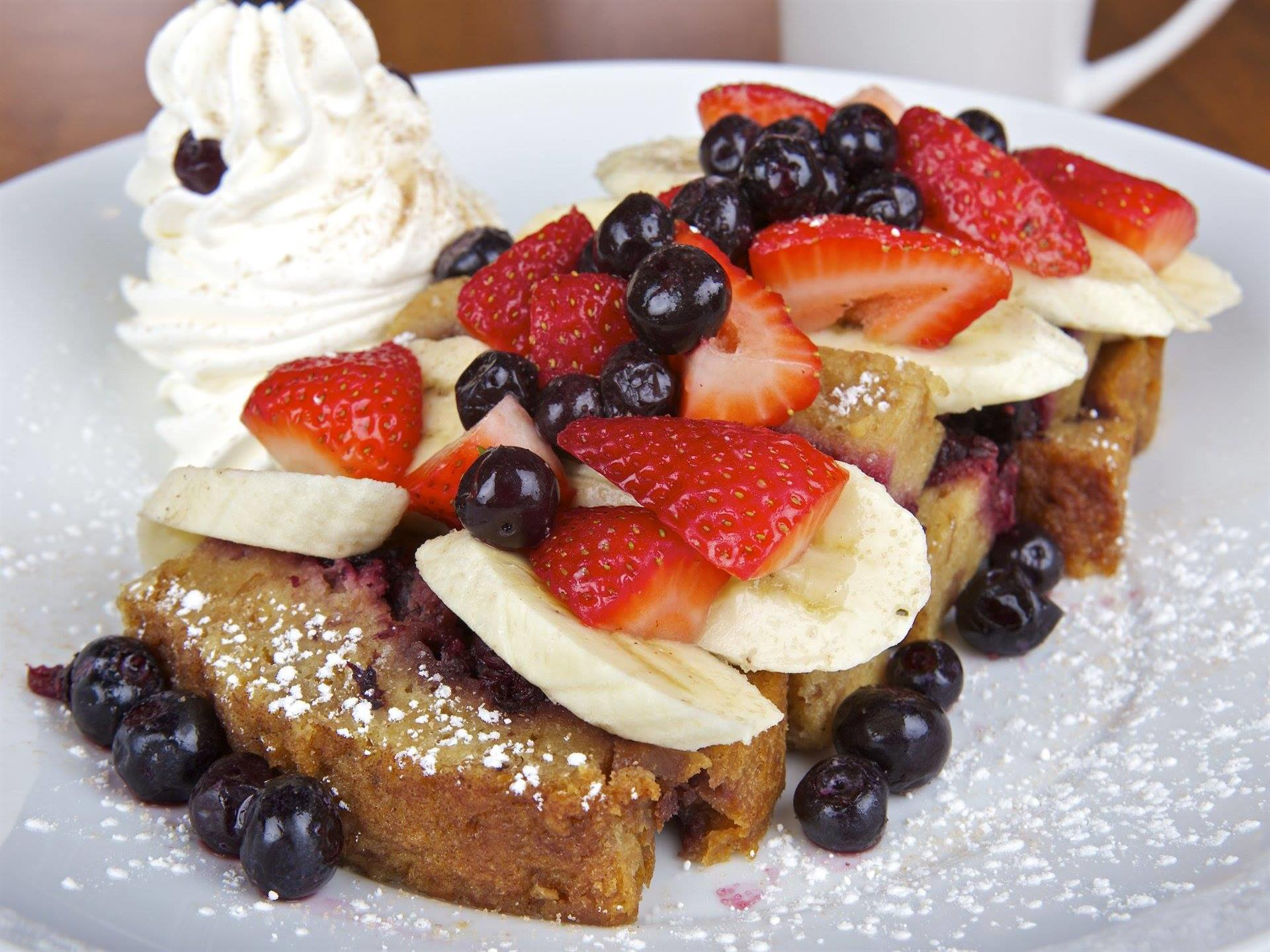 French toast topped with strawberries, bananas, blueberries, whipped cream and powdered sugar.