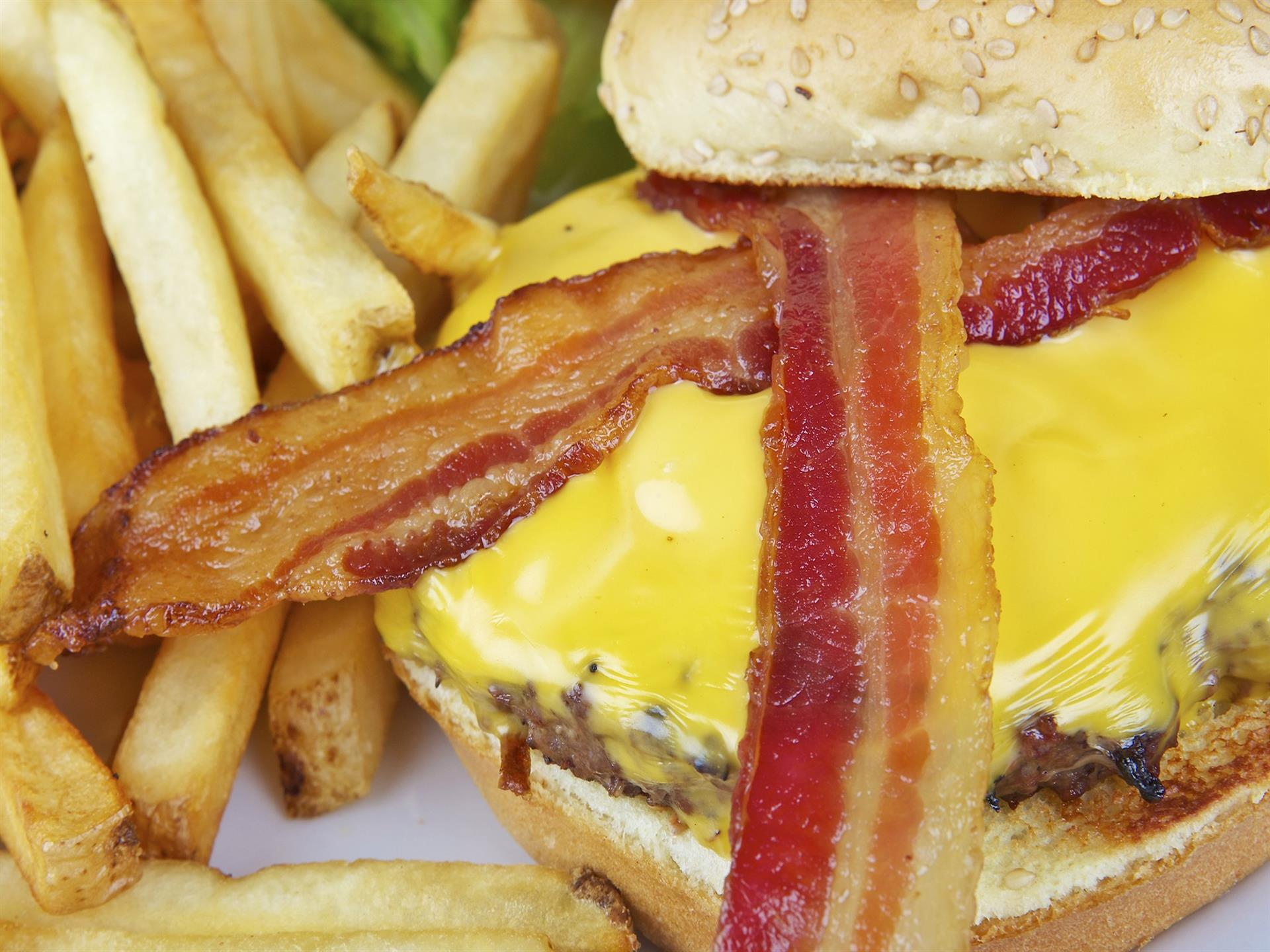 Bacon cheeseburger on a seeded bun with a side of French fries