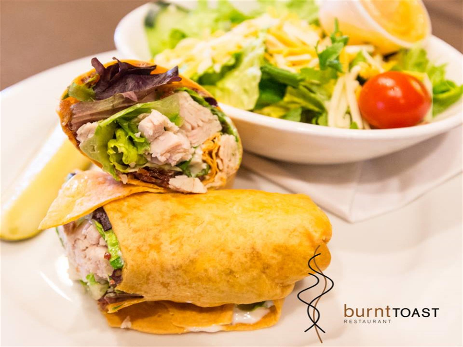 Wrap with chicken and lettuce cut in half with a side salad.