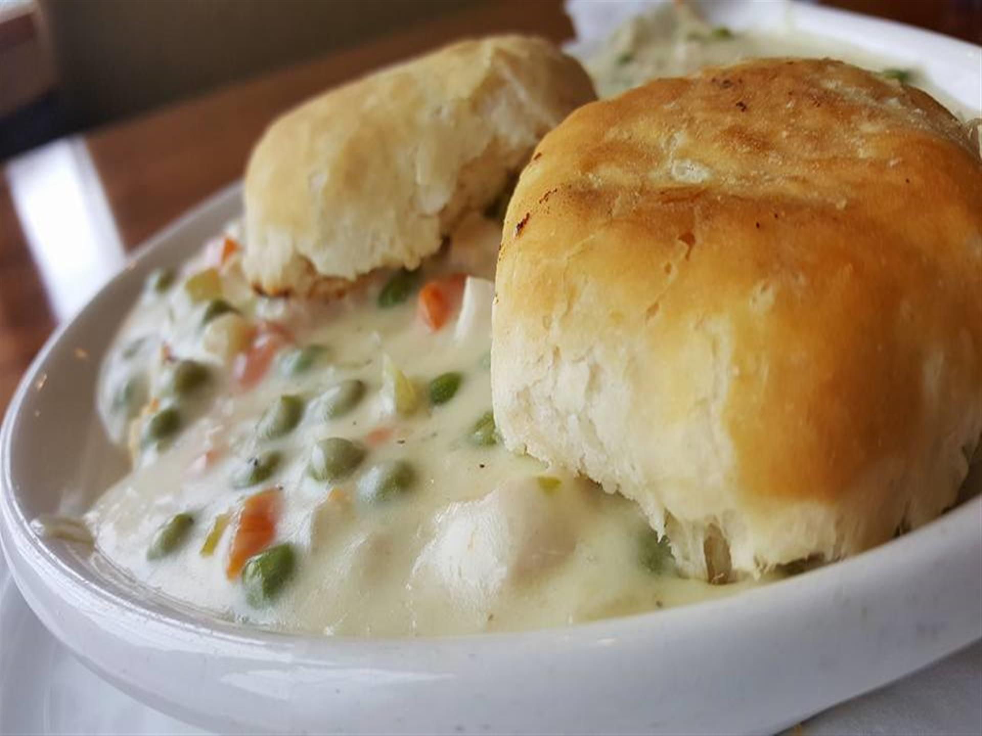 Chicken pot pie with biscuits in a white bowl.