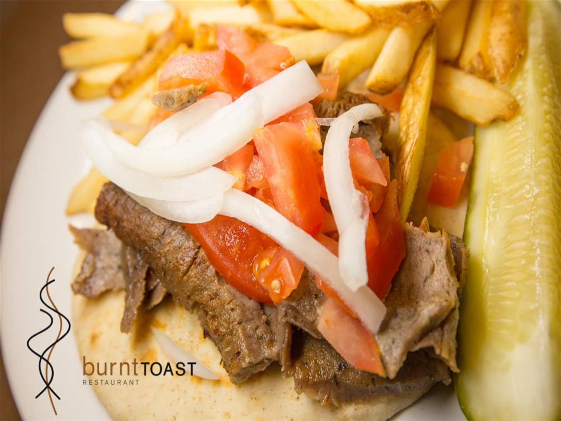 Close up of a beef gyro with tomato and onion. French fries on the side.