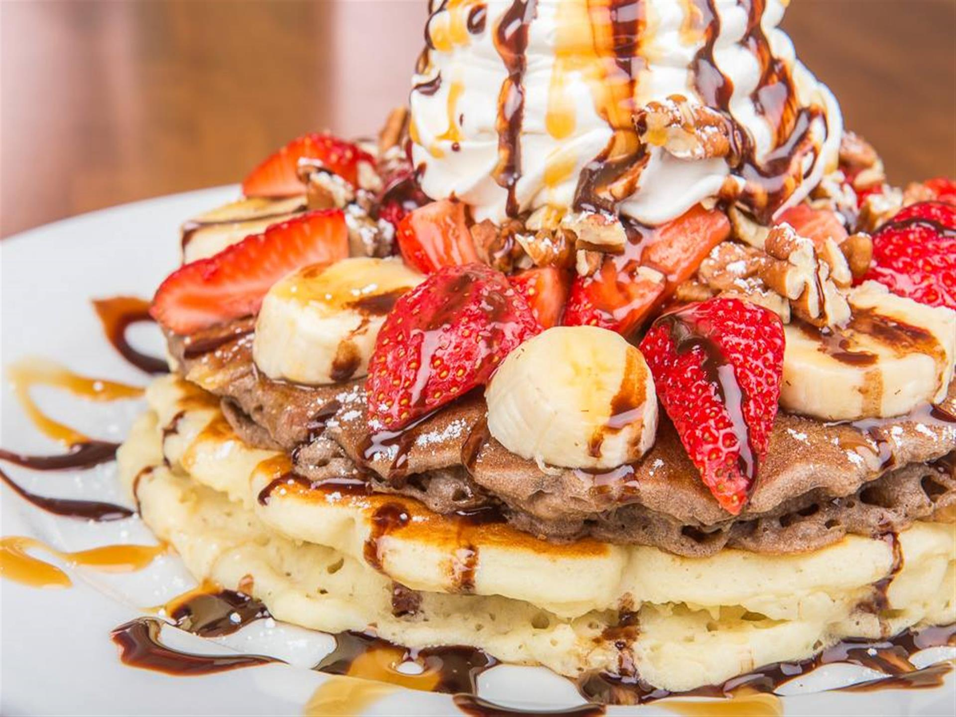 Stack of pancakes topped with strawberries, bananas, whipped cream, maple syrup and chocolate syrup.