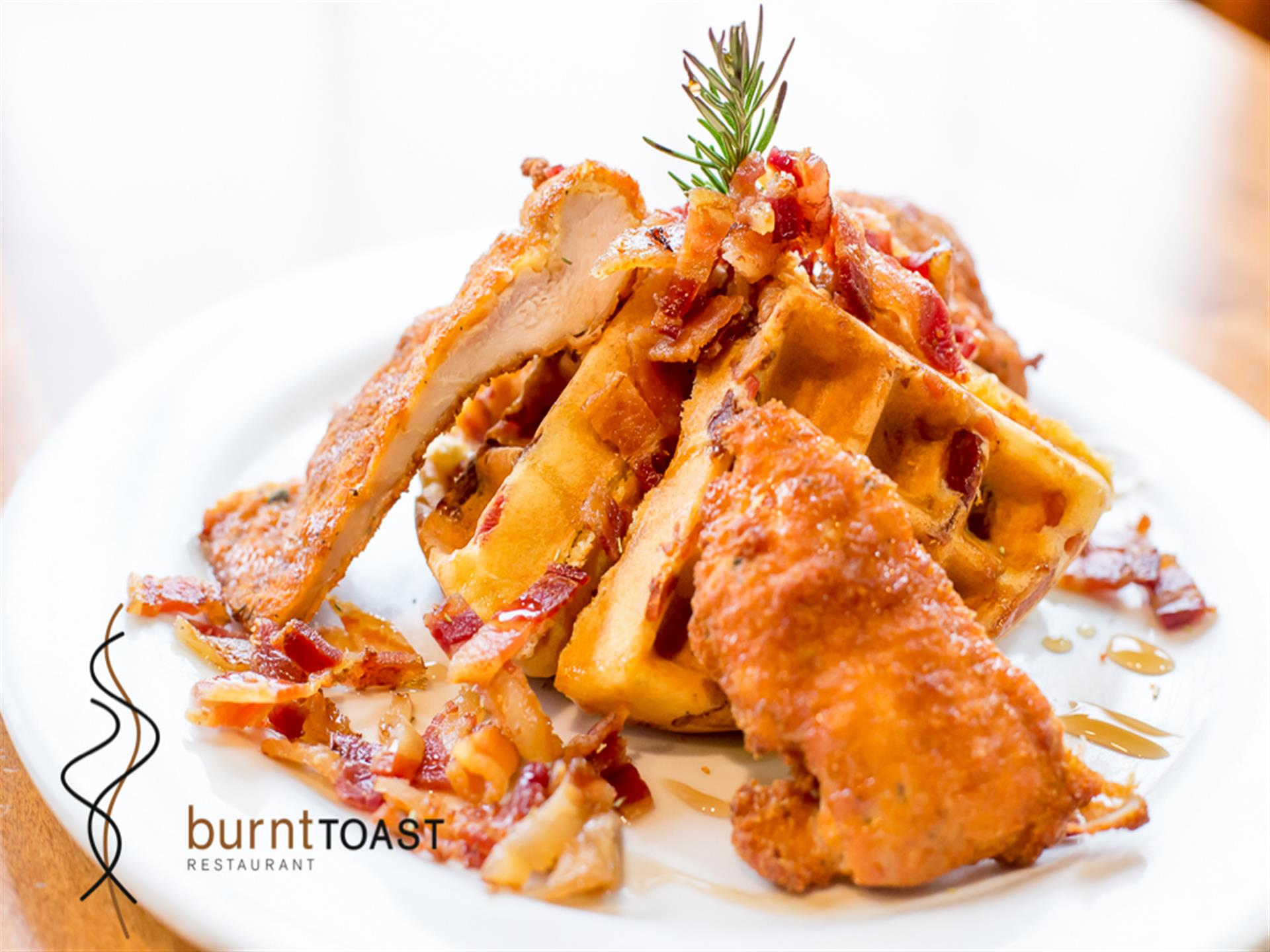 Chicken & Bacon & Waffles. Enjoy succulent layers of flavor starting from the bottom with our homemade bacon stuffed waffles & special rosemary fried chicken breast, then topped with our thick & juicy bacon.