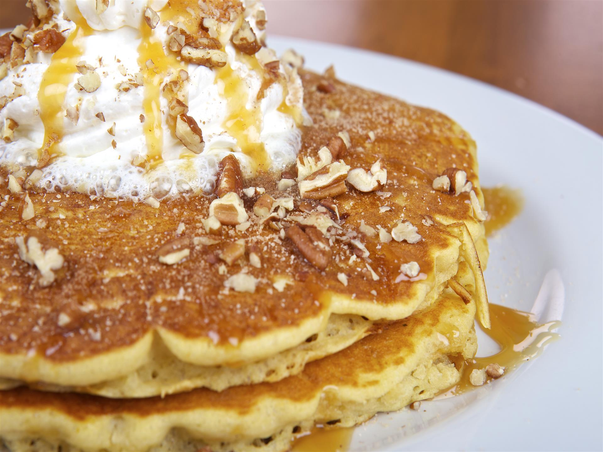 Stack of golden buttermilk pancakes topped with whipped cream, maple syrup and pecans,