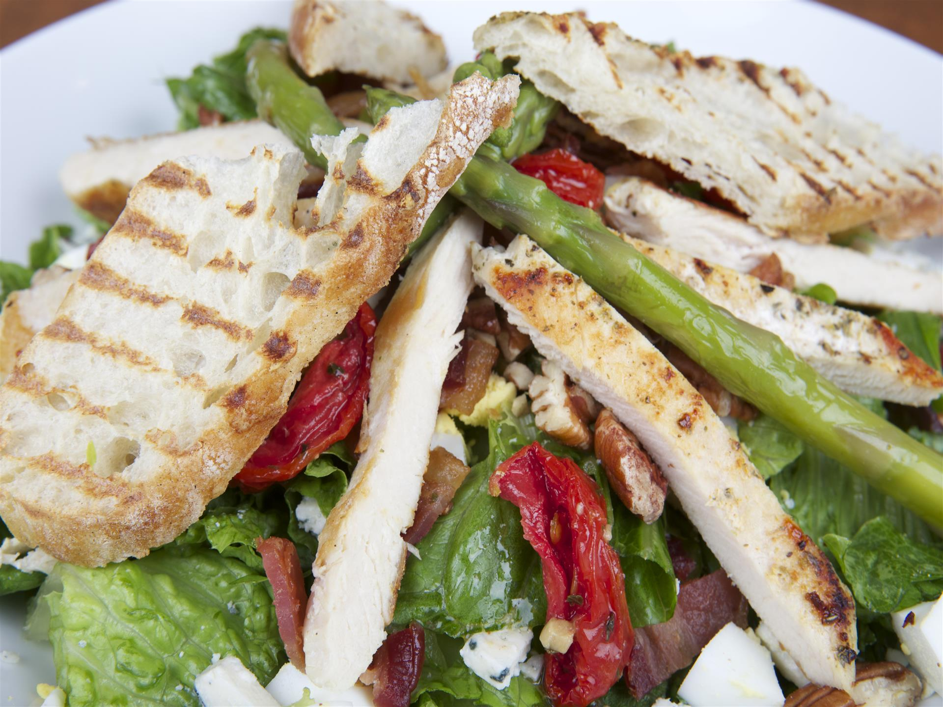 Asparagus Chicken Cobb Salad. A blend of mixed greens topped with asparagus, grilled chicken, chopped hard boiled egg, gorgonzola cheese, marinated sun-dried tomatoes, walnuts & bacon