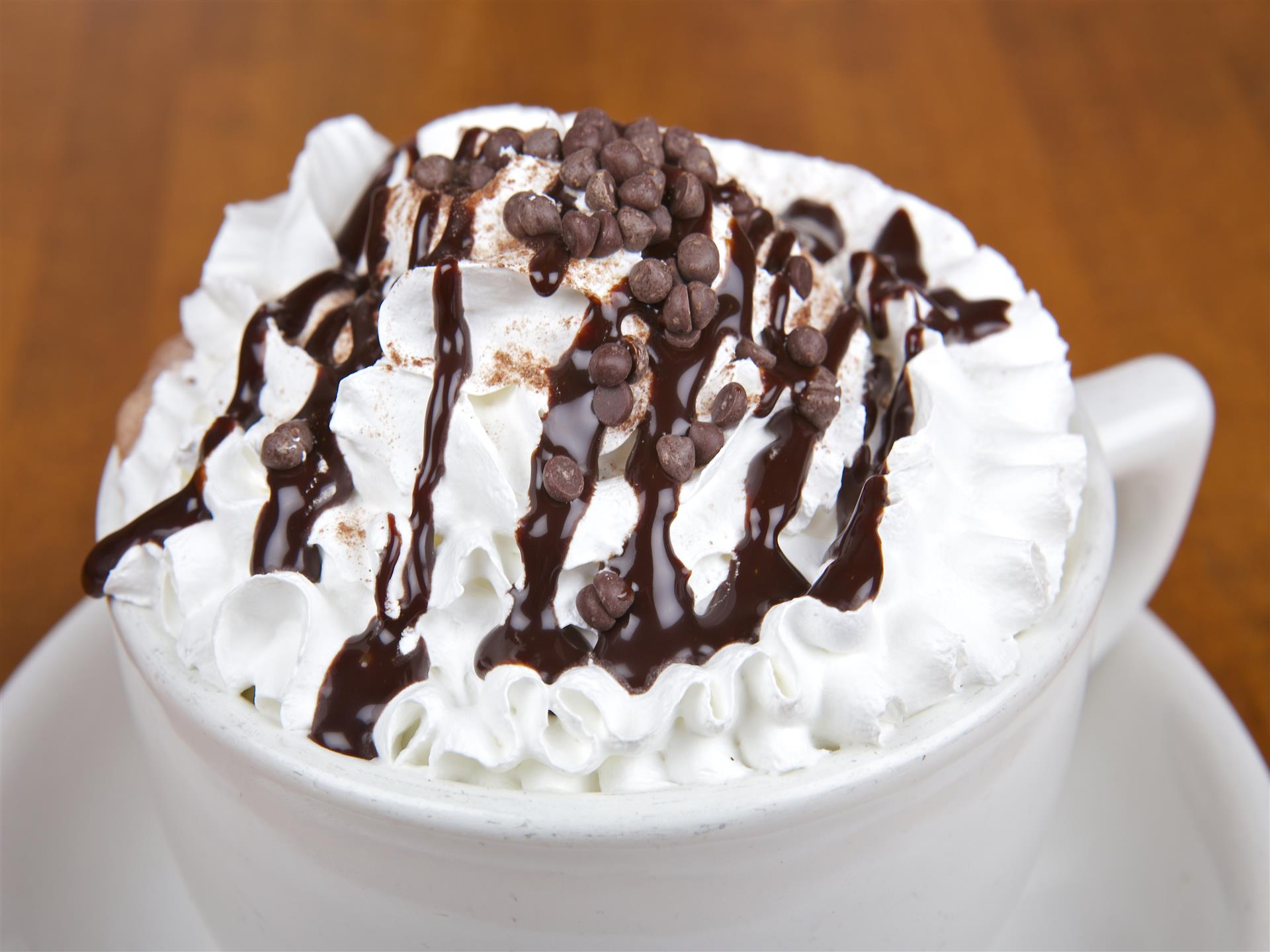 Hot chocolate in a white mug with whipped cream, drizzled chocolate syrup, chocolate chips and cinnamon