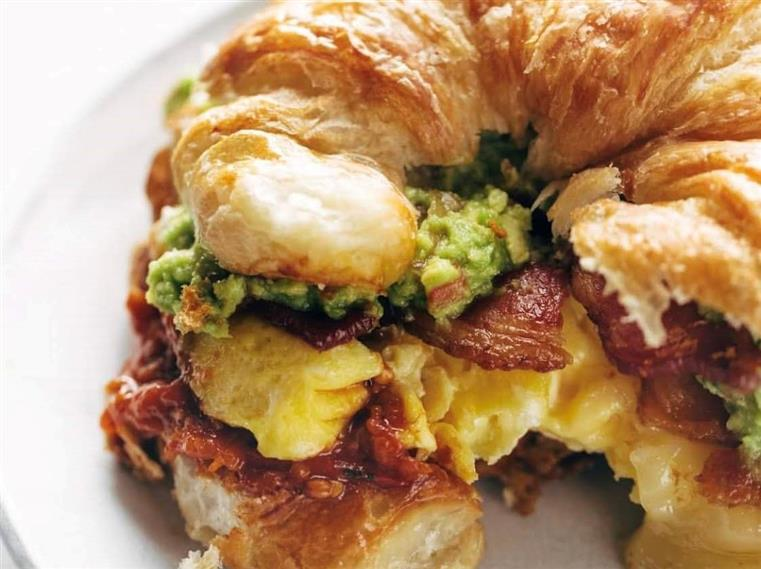 Baja Breakfast Croissant. Scrambled eggs, thick bacon, our homemade garlic butter tomato sauce & our flavorful guacamole. Served with hash browns.