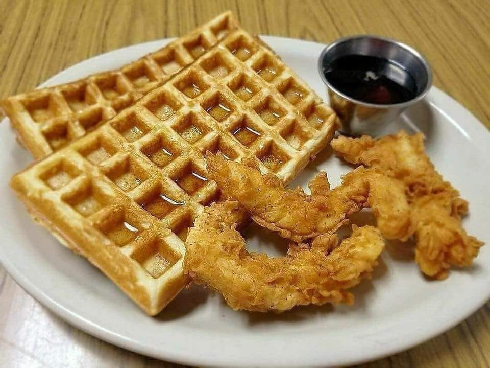 Chicken strips on a plate with waffles and maple syrup
