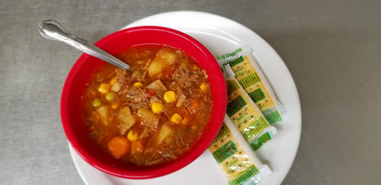 Minestrone soup in a bowl with a spoon and crackers on the side in packaging
