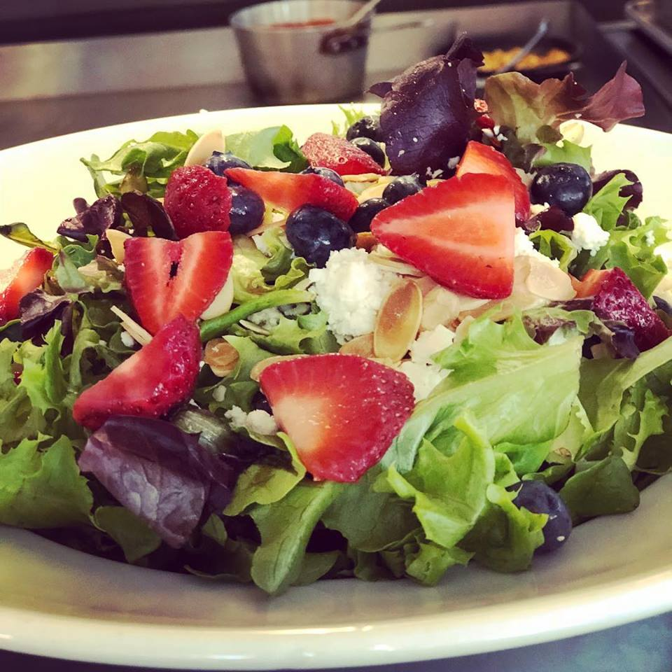 Mixed green salad with strawberries, blueberries and sliced almonds