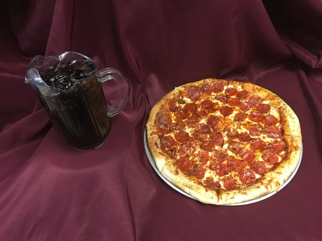 Large pepperoni pizza with a pitcher of soda