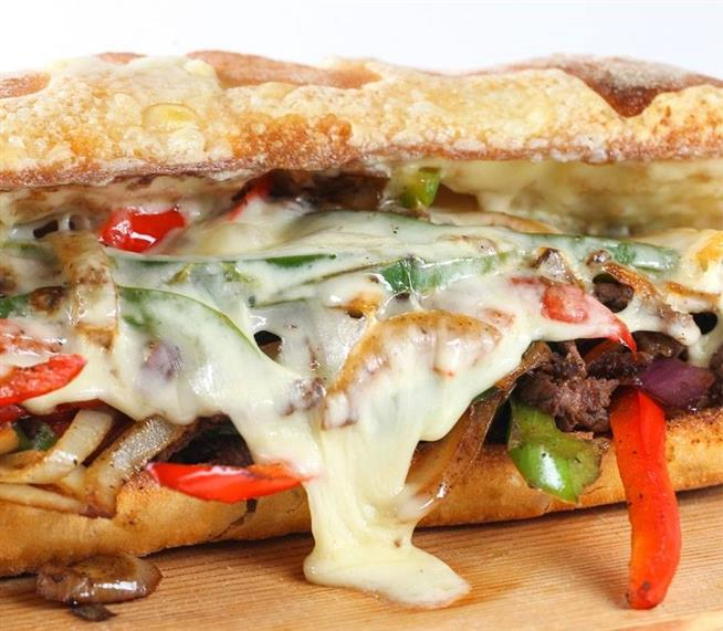 Cheese and steak sandwich with sauteed peppers and onions on a hoagie