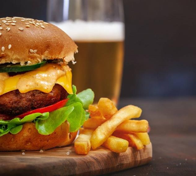 Cheese burger with lettuce, tomato, spicy sauce and jalapenos on a seeded bun with French fries and a beer in the background