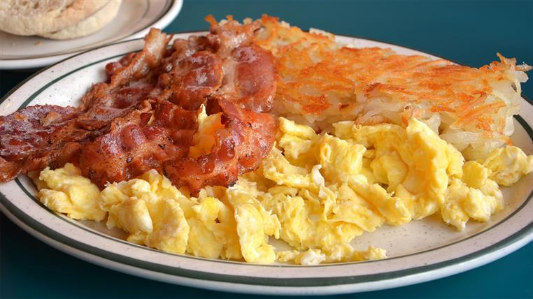 Plate with scrambled eggs, bacon and hashbrowns.