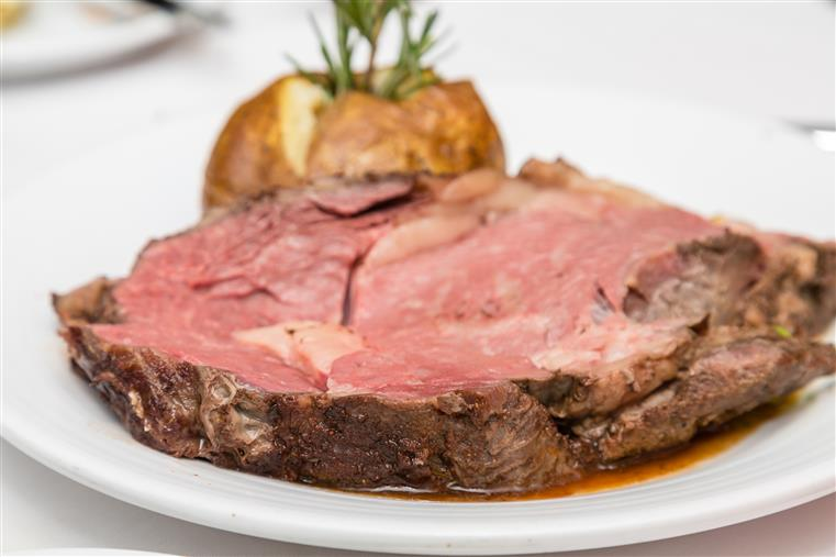 Prime Rib on a white plate with a baked potato on the side.