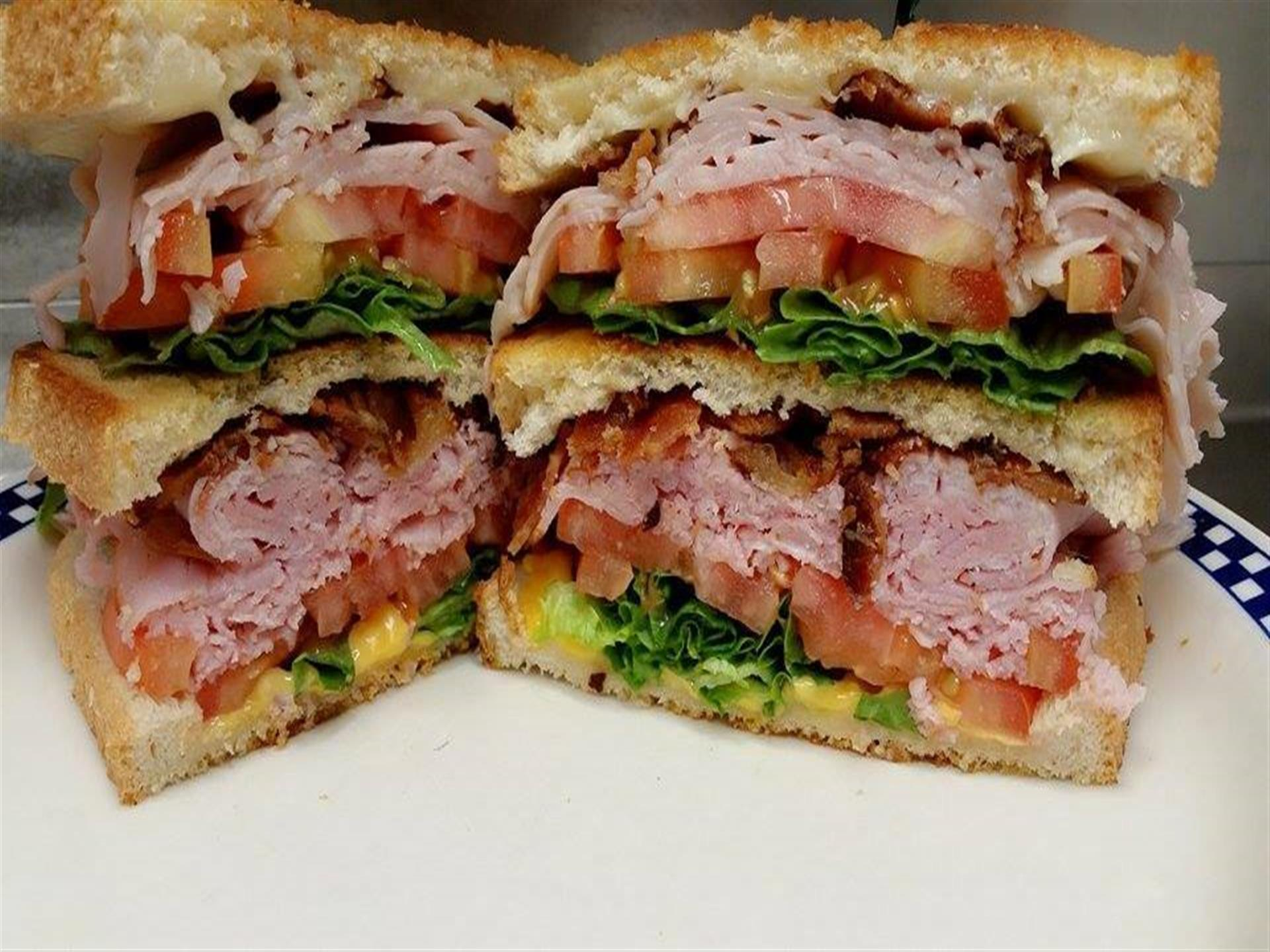 huge sandwich filled with meat, lettuce, tomatoes