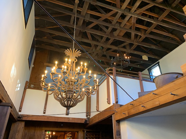 Interior view of chandelier hanging from wooden exposed beams