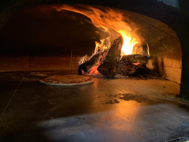 Inside of coal oven with pizza cooking next to flames