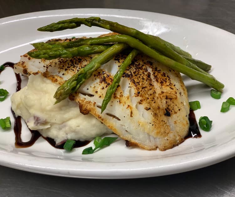 Cod fillet over mashed potatoes with asparagus