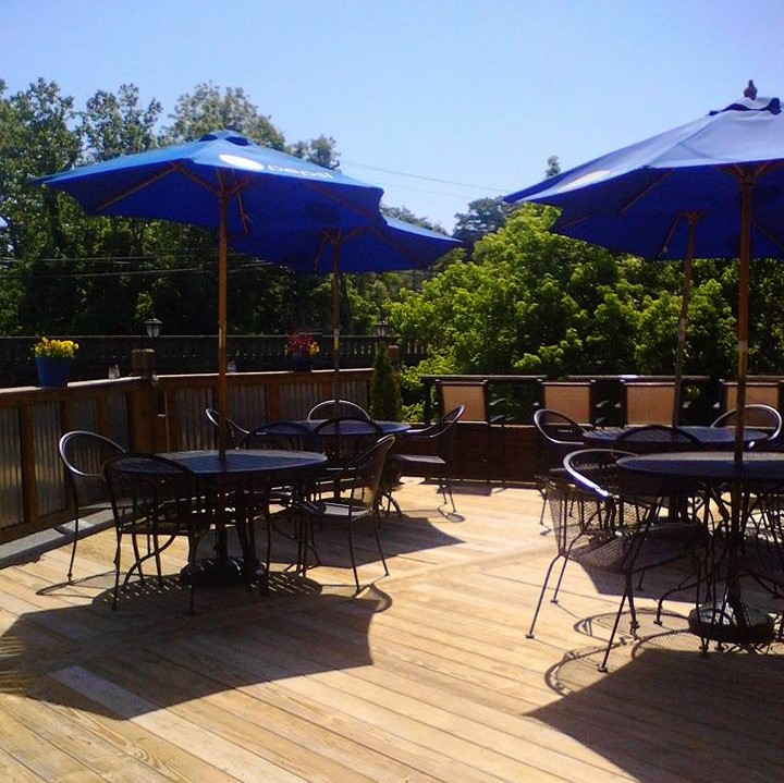 Outside patio area with tables and chairs with open blue umbrellas