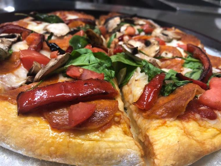 Pepperoni pizza with mixed grilled vegetables and spinach.