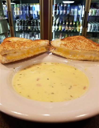soup in a bowl with grilled cheese cut in half