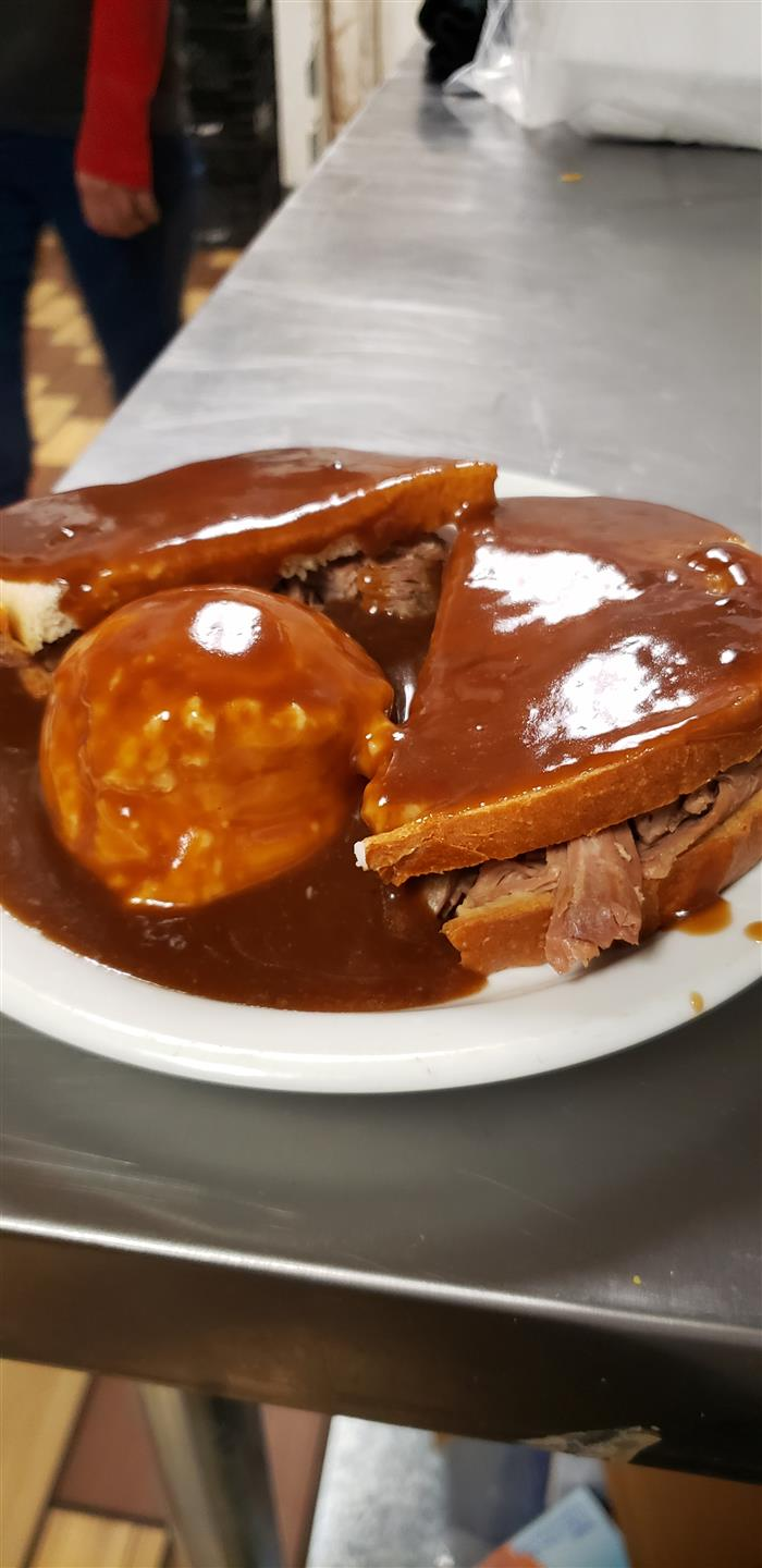 mased potato and a beef sandwich smothered in a generous amount of brown gravy