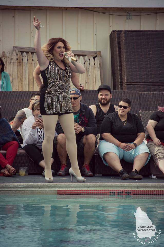 Performer singing by a pool in front of guests