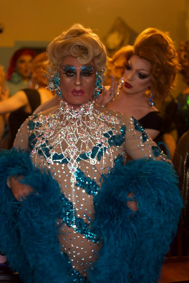 Miss Fire Island Pageant contestant wearing a tiara and a blue sequin dress posing for a photo