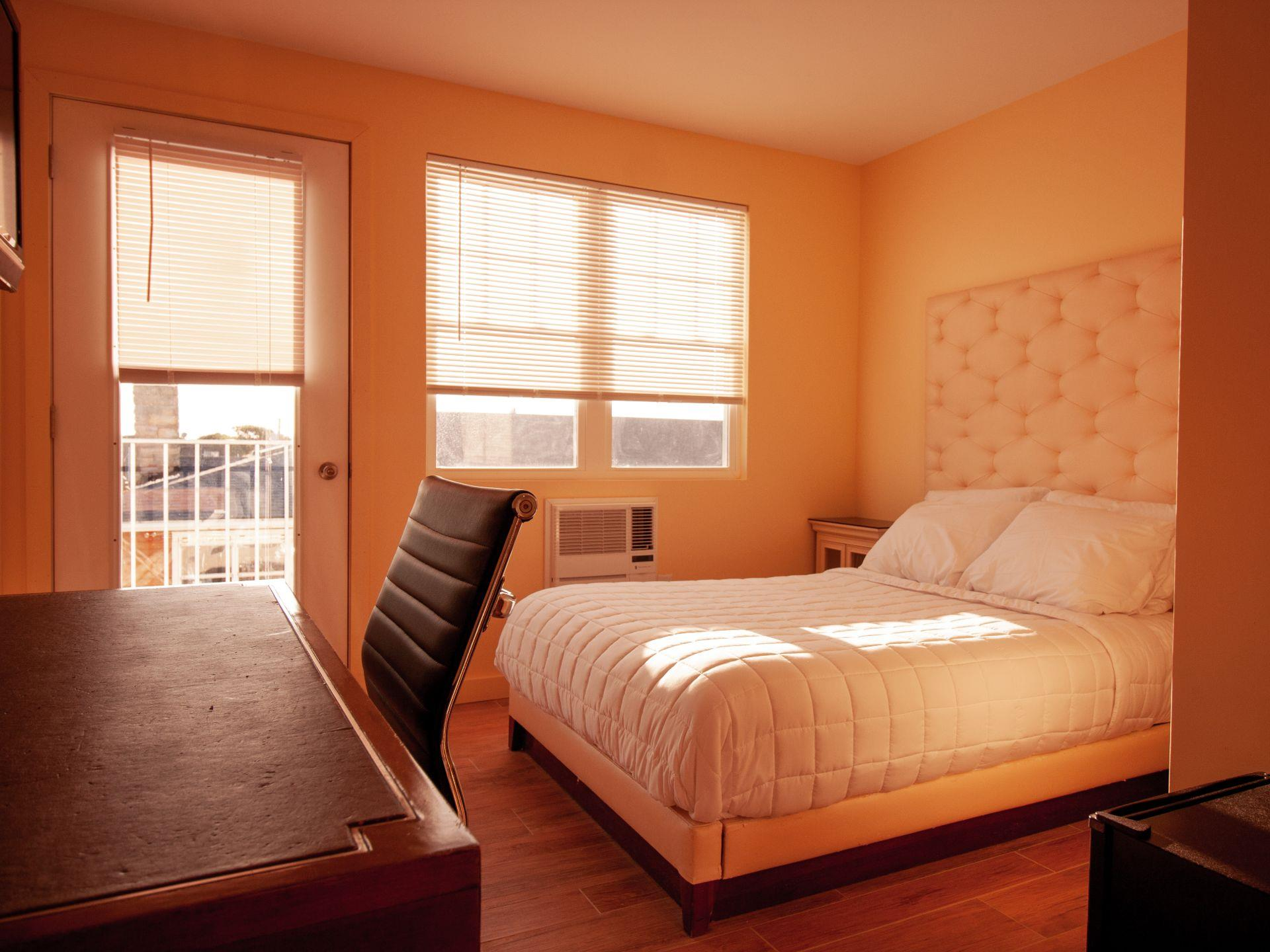 Standard room with a full size bed, desk and chair with a door leading to a balcony