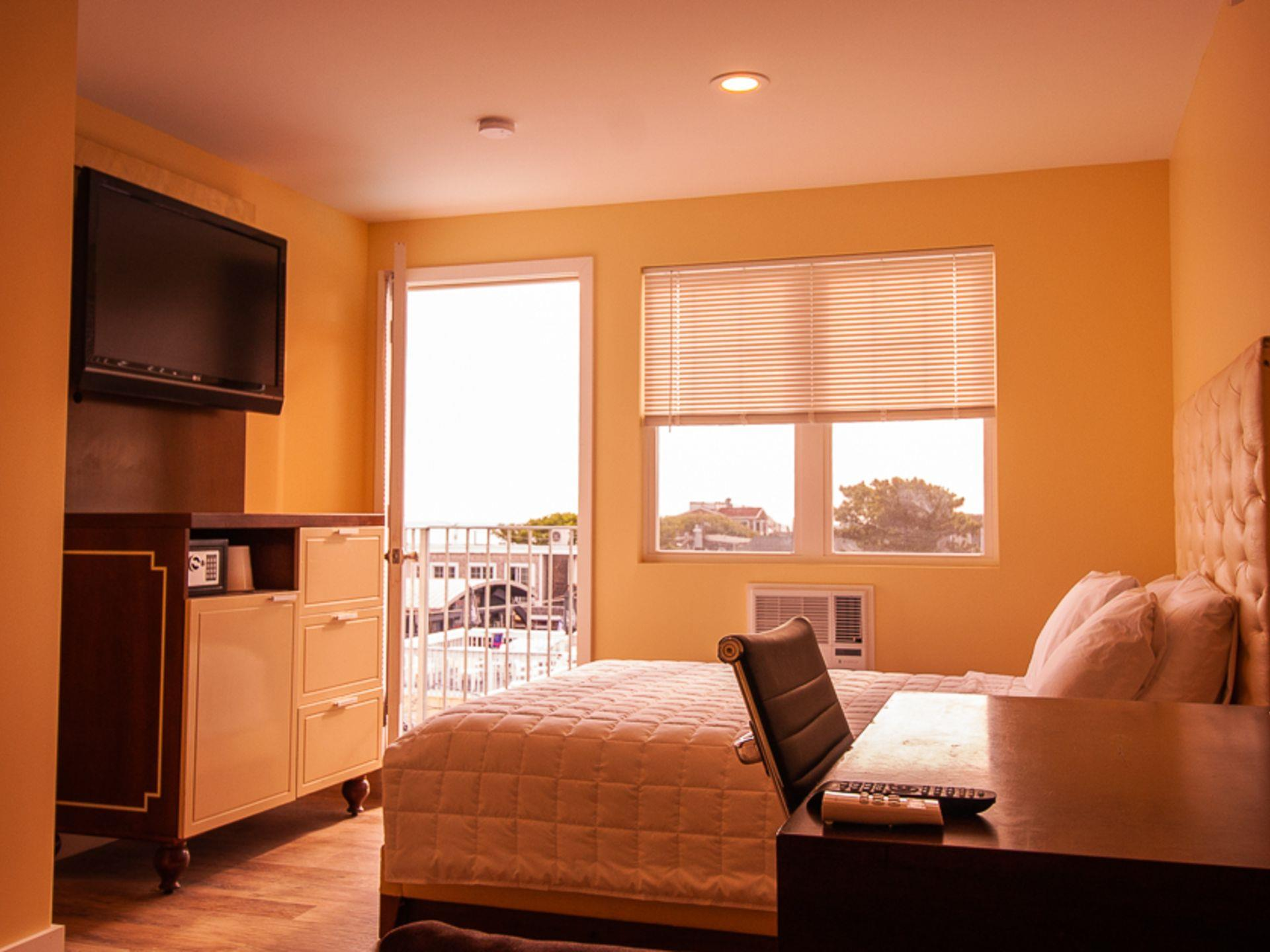 Standard room with a full size bed, desk and chair, a dresser and a tv on a wall with a door leading to a balcony