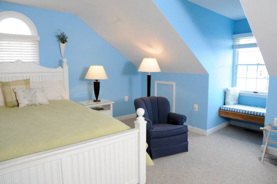 Bedroom with light blue painted walls, a night stand with lamp and a small blue side chair