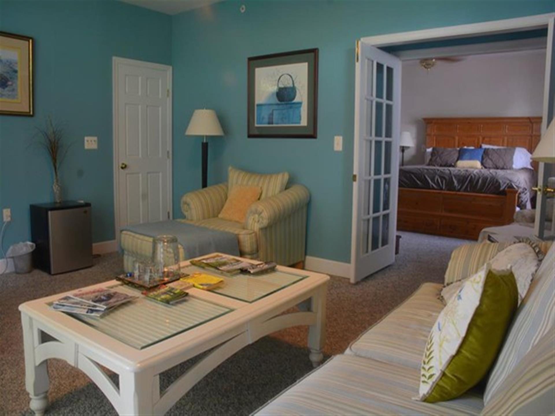 Sitting area in Suite 2. Bright blue colored walls and relaxing beach decor.