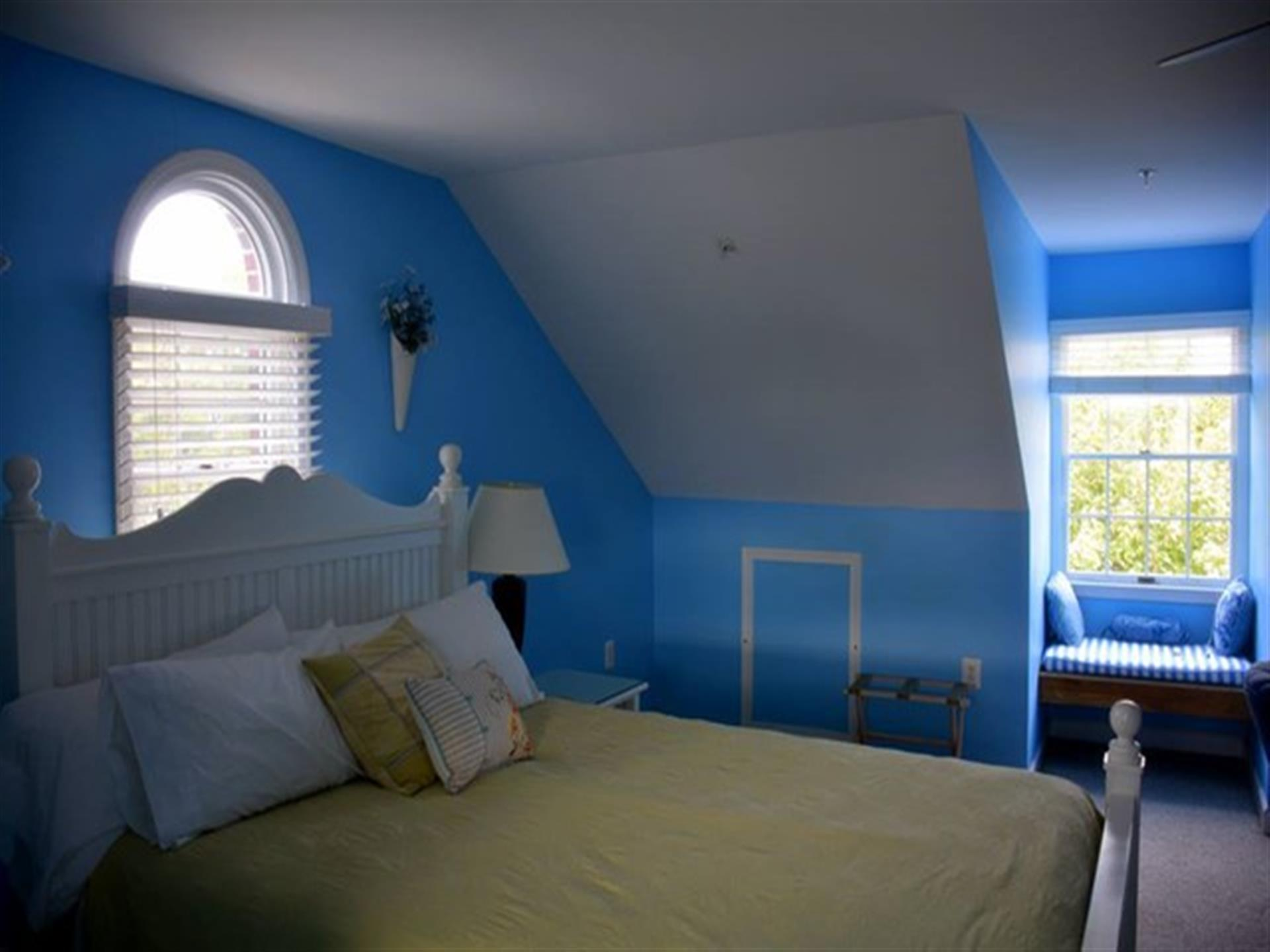 Suite 4 bedroom. Sky blue walls, white furniture and a queen-size bed.