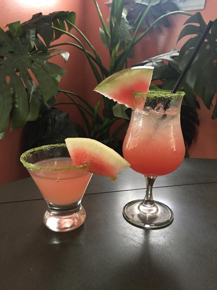 Two watermelon mixed drinks on a table-top