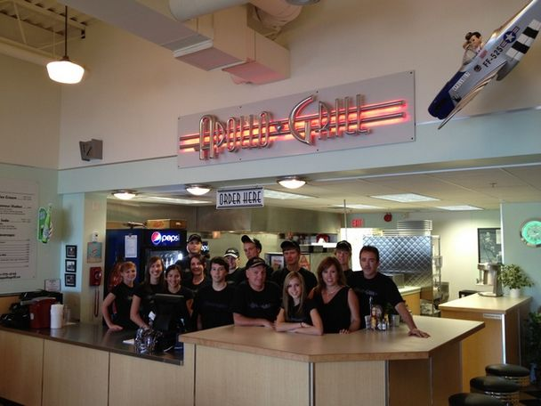 Interior view of restaurant with 14 staff members smiling taking a group photo below Apollo Grill sign with red light
