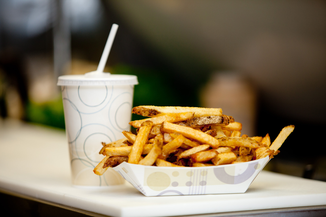 Heaping serving of french fries in paper serving boat dish with a drink in cup with straw behind it on cutting board