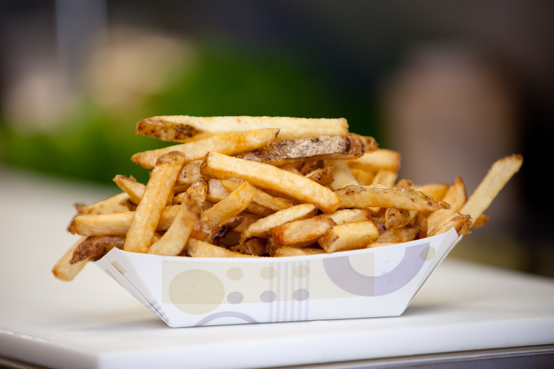 Heaping serving of french fries in paper serving boat dish on cutting board