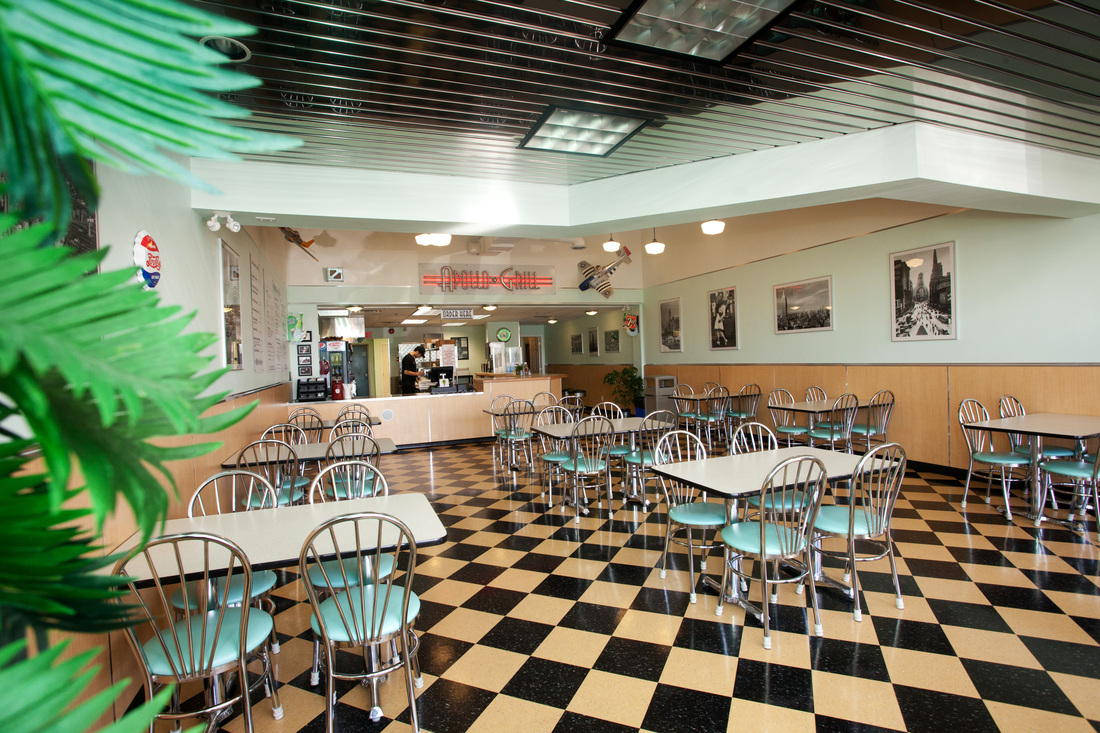 Interior view of restaurant with view of plants on left side of frame, retro style furniture and deco with checkerboard tile floor
