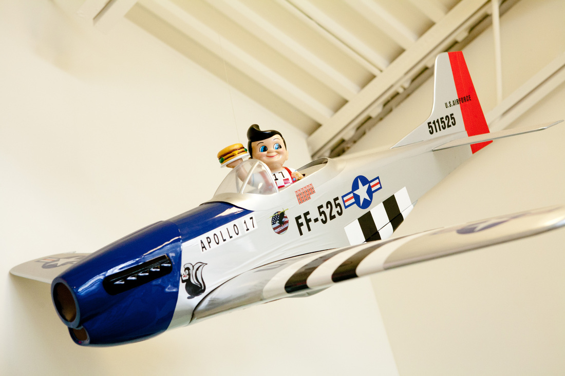 Puppet figurine holding a model burger in a model airplane decaled with 'Apollo 17 FF-525' on side, hanging from ceiling