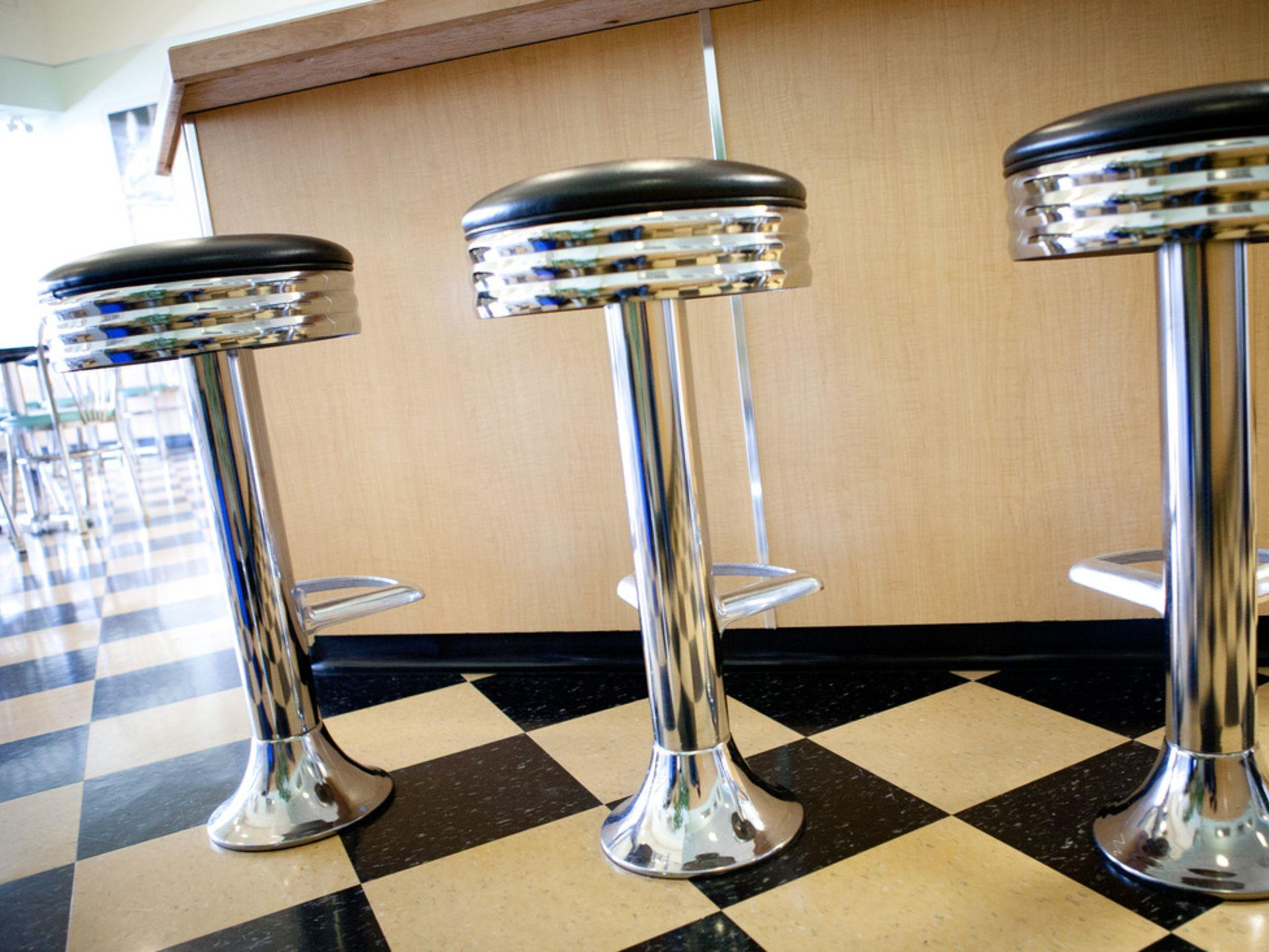 3 Metal retro-style stools at counter with checkerboard styled tiles on floor