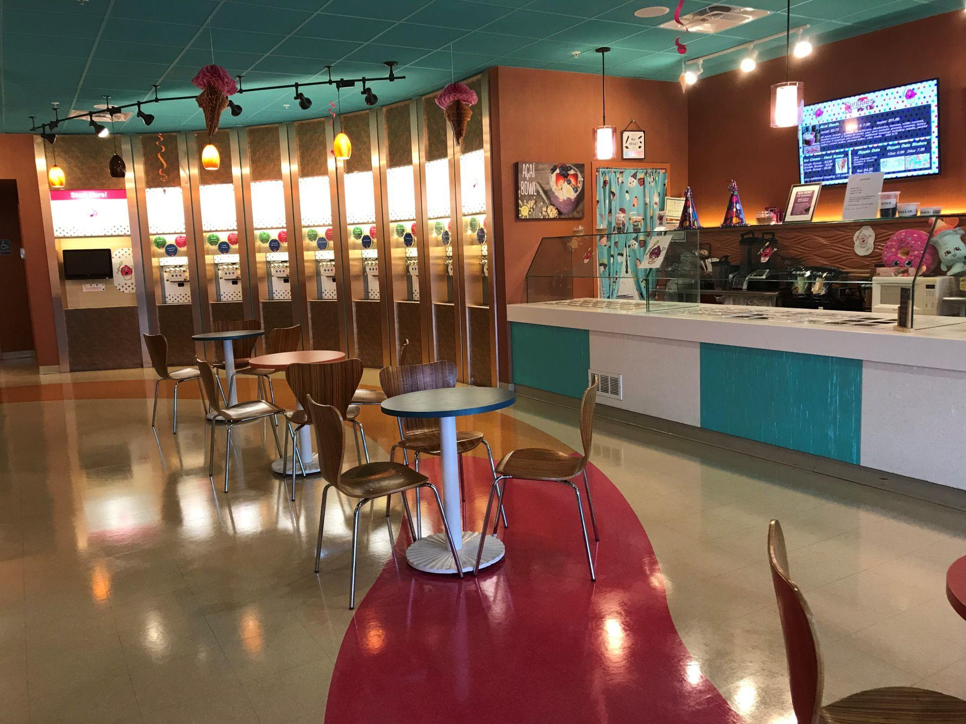 Interior of a self-serve ice cream shop tables and chairs in the center, a counter-top with ice cream toppings and a wall of self-serve ice cream machines