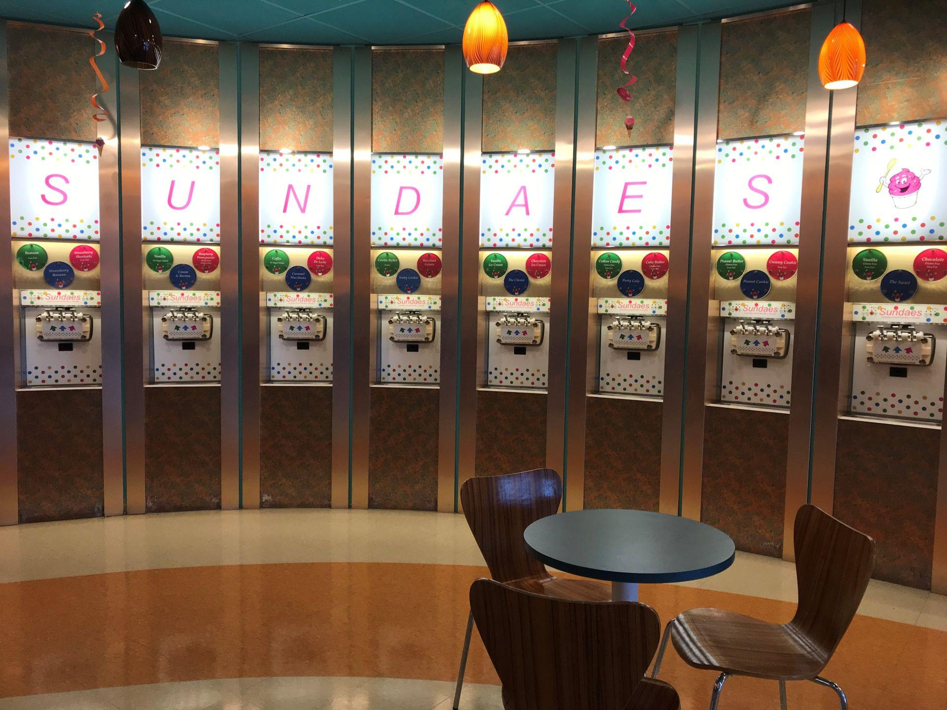 Self-serve ice cream machines lined up along a wall with Sundaes branding
