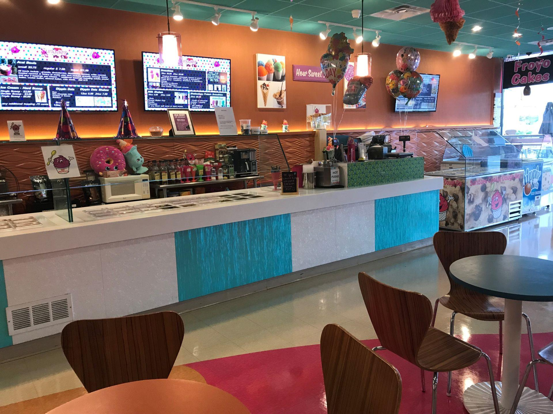 Interior of a self-serve ice cream shop with tables and chairs and a counter-top with containers of assorted ice cream toppings and a cash register