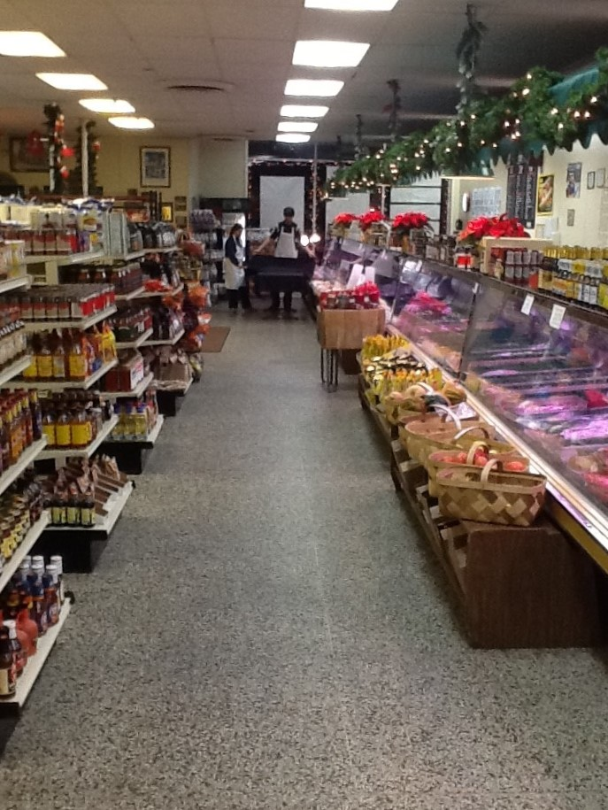 Interior of K&K Portage Market with shelves of assorted grocery items and a display case with raw meats